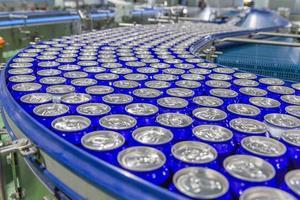 latas na correia transportadora na fábrica de bebidas foto