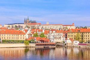 cidade velha colorida e castelo de Praga com o rio Vltava, república checa foto