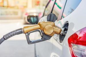carro branco em posto de gasolina sendo abastecido com combustível na Tailândia foto
