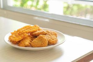 nuggets de frango frito com batatas fritas foto