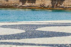 calçadão da praia de copacabana com o mar e o muro do forte foto