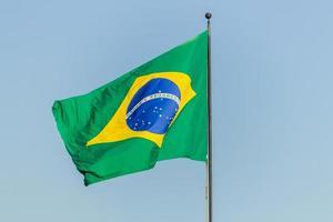 bandeira brasileira hasteada com fundo de céu azul foto