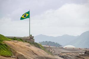 bandeira brasileira em cima de rocha no forte de copacabana foto