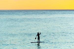 silhueta de homem com stand up paddle na praia de ipanema, no rio de janeiro, brasil foto