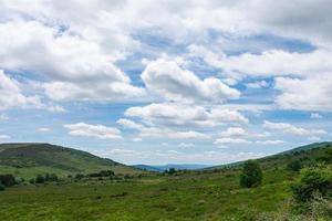 prado de alta montanha com um céu cheio de nuvens foto