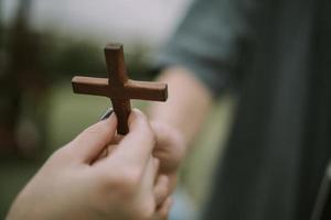 mão com cruz. conceito de esperança, fé, cristianismo, religião, igreja online. foto