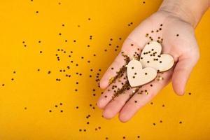 mão segurando dois corações em fundo amarelo foto