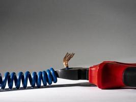 alicate vermelho e fio trançado azul em fundo branco foto