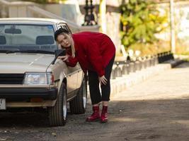 jovem loira com roupas vermelhas olhando no espelho de um carro velho foto