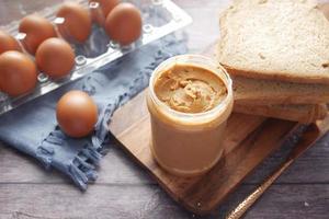 vista superior de manteiga de amendoim e um pão no prato em fundo preto foto