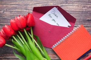 envelope, carta e flor de tulipa na mesa foto