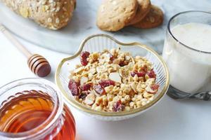 cereal matinal na tigela, pão e mel no fundo branco foto