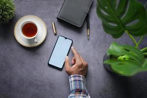 vista superior da mão do homem usando telefone inteligente em fundo preto foto
