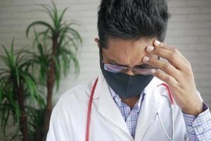 médico triste e deprimido cobrindo o rosto com as mãos foto