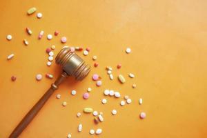 vista superior do martelo e comprimidos médicos em fundo laranja foto