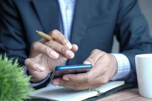 mão de jovem usando telefone inteligente e escrevendo no bloco de notas na mesa foto