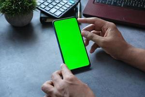 vista traseira da mão do homem usando o telefone inteligente na mesa do escritório foto
