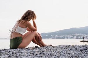 jovem mulher deprimida sentada na praia, olhando para longe, vista traseira foto