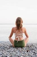 retrovisor de uma jovem meditando na praia foto
