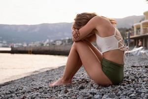 jovem mulher deprimida sentada na praia foto