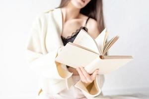 mulher com roupas confortáveis em casa lendo um livro sentada no chão foto