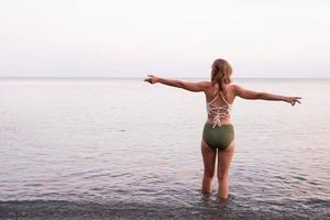 jovem em pé na praia pedregosa com os braços estendidos foto