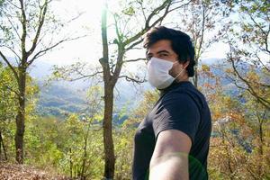 homem usando uma máscara facial e tira uma selfie na natureza. foto