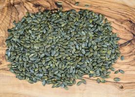 sementes de abóbora torradas na madeira de oliveira foto