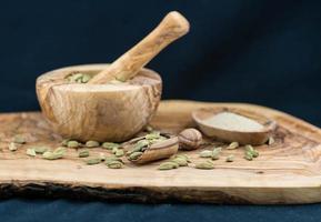 cardamomo verde em madeira de oliveira foto