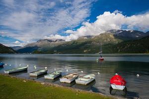 pequenos barcos de pesca atracados no lago da montanha foto