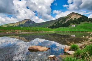 pequeno lago alpino com montanhas refletidas é uma cabana alpina foto
