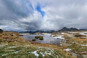 pequeno lago alpino com ilhas de prados no outono foto