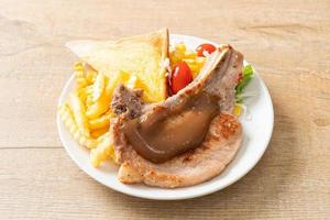 bife de costeleta de porco com batatas fritas e mini salada em prato branco foto