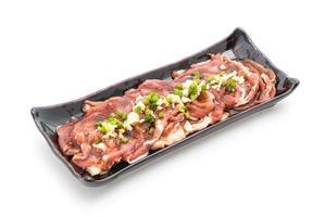 carne de porco fresca fatiada com molho no fundo branco foto