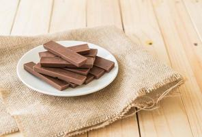 barras de chocolate no fundo de madeira foto