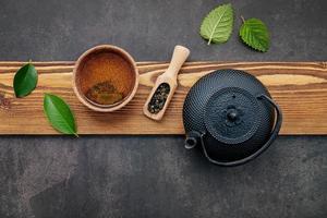 bule de chá preto de ferro fundido com chá de ervas em fundo de pedra escura foto