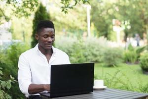 empresário afro-americano, trabalha em um laptop em um café, freelancer foto