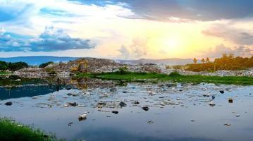 água poluída e grande pilha de lixo da montanha e poluição foto