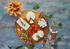 queijos de diferentes formatos e sabores em prato redondo de madeira foto
