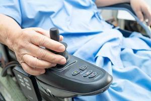 paciente sênior asiática em cadeira de rodas elétrica. foto