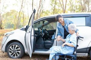 ajudar paciente idosa asiática sentada em uma cadeira de rodas a chegar ao carro foto