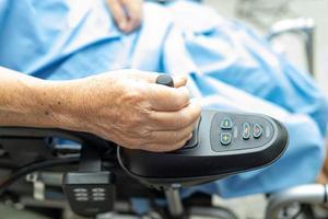 paciente idosa asiática em cadeira de rodas elétrica com controle remoto foto