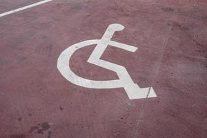 placa de estacionamento branca para deficientes físicos pintada em um piso vermelho foto