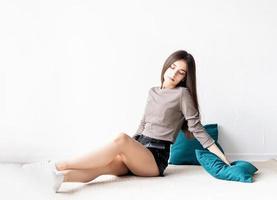mulher com roupas casuais sentada no chão com almofadas foto