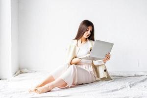 mulher sentada no chão fazendo projeto freelance no laptop foto