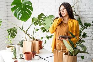 jardineira trabalhando em um tablet digital e fazendo uma ligação foto