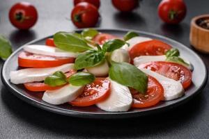 salada caprese italiana com tomate fatiado, queijo mussarela foto