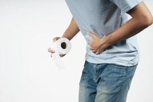 homem segurando seu estômago e lenço de papel, sofrendo de diarreia. foto