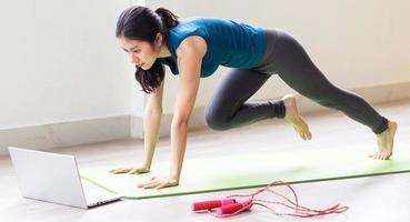 jovem asiática fazendo exercícios no chão sozinha foto