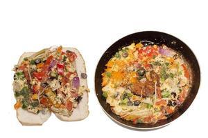 omelete de vegetais em uma panela de ferro preta em um fundo branco foto